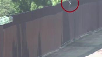 Trafficante porta bambina oltre il muro tra Usa e Messico